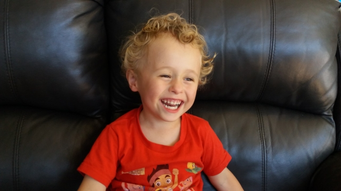 Happy toddler boy smiling on couch